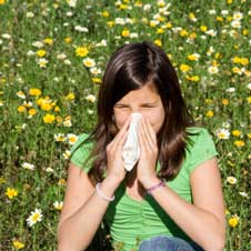 Girl suffering from allergies in a field of flowers.