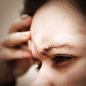 Woman with her hand on her forehead suffering from a headache or migraine.
